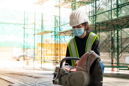 Young Asian female engineer wearing a medical mask to cover her mouth and wearing a white safety helmet A small concrete slab cutting machine is being prepared in the construction Zone.