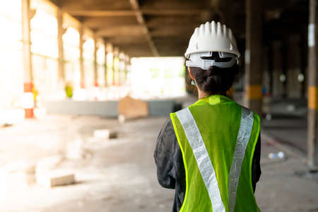 Behind a woman, a construction engineer wearing a hat and a green safety vest, stands looking at work in the construction zone. Standard-Bild