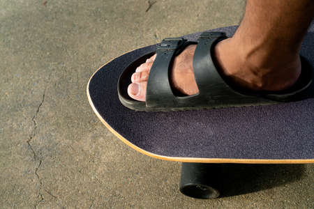 men's feet In sandals, stepping on a black Surf Skate on the sand in the park. Standard-Bild