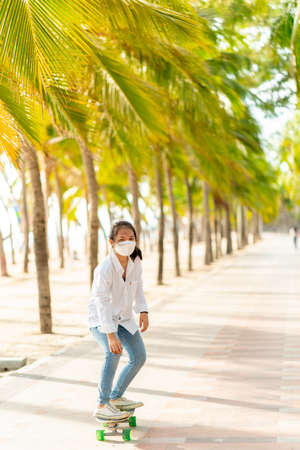 Teen Asian girl in white shirt and jeans is practicing for a play. Surf skating along the beachfront promenade behind many coconut trees, Bangsaen, Thailand.