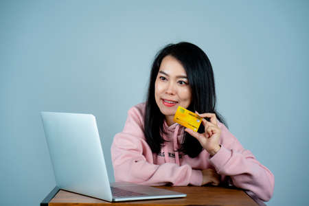 Portrait of an Asian girl wearing a pink shirt. in mobile credit card sitting on a laptop computer online shopping with happy expression, behind gray background in studio