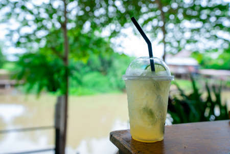 Lemon soda is placed in a plastic cup with a straw on a wooden table in a canal-side restaurant.
