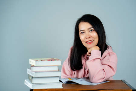 Portrait of an Asian girl wearing a pink shirt. reading a book nice back background gray studio