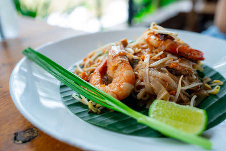 Pad Thai with Fresh Shrimp, a delicious Thai food with big prawns. Lime by the side is placed in a plate lined with banana leaves.