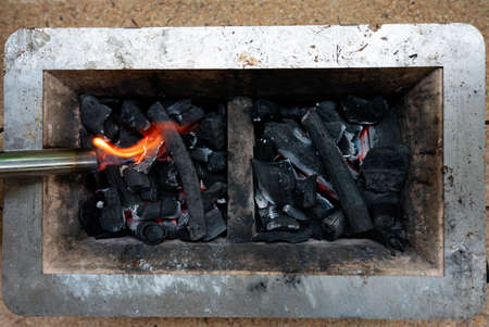 The charcoal grill is ignited so that the charcoal is turned off and ready for the food to be grilled.
