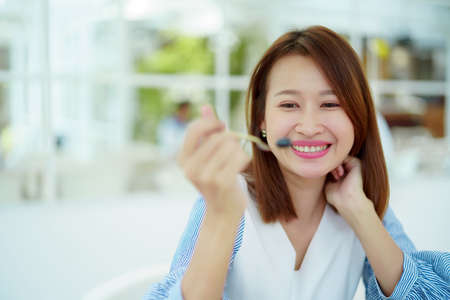 A beautiful Asian portrait is taking a spoonful of cakes on the table and eating them with happy eyes and expressions in the bakery. Standard-Bild