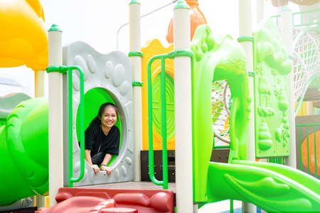 Asian teenage girl wearing a black shirt Happy playing in the playground on a clear day.