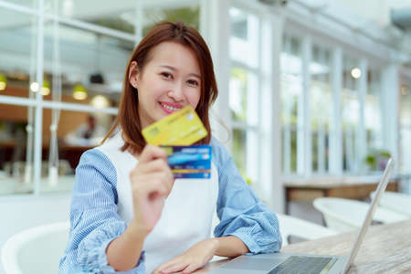 A beautiful Asian woman in a white shirt is sitting in front of a computer with a credit card in her hand to prepare for online shopping. Her face looks very happy in a bakery.
