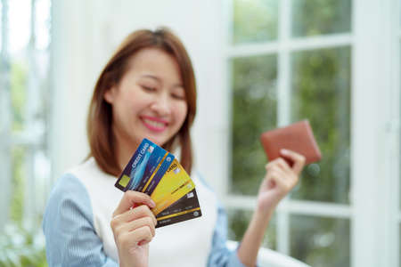 Several credit cards are in the hand of a beautiful Asian woman with the woman out of focus. Happy smiling faces preparing for online shopping.