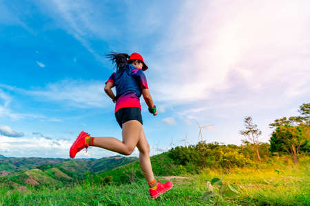Asian female trail runners, wearing sportswear, are practicing running and jumping on the high mountain behind a beautiful view.. There is a field of wind turbines generating electricity in the background.