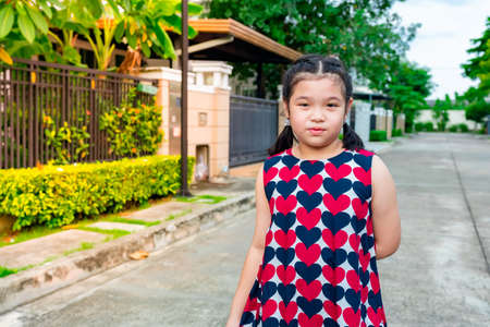 Asian girl happily walking and relaxing in front of the house. with a smiling face in the morning Standard-Bild