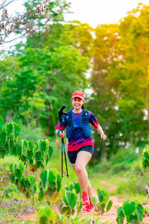 Asian female trail runners, wearing runners, sportswear, practice running on a dirt path in a forest. With a happy mood, there were many green trees in the background.