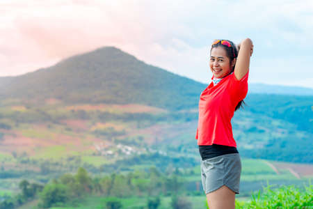 Half-body photo of a female trail runner wearing pink runner, sportswear, smiling, looking at the camera. on the gravel ground on a high mountain with a happy mood, on a clear day Behind is a mountain view.