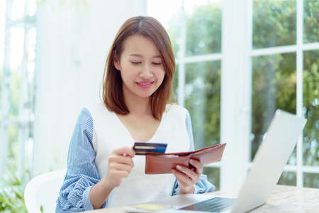 A beautiful Asian woman wearing a white shirt with a credit card comes out of her wallet smiling happily in front of her laptop preparing for online shopping. Standard-Bild