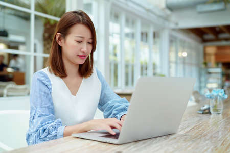 A beautiful woman wearing an Asian white shirt is sitting in front of a laptop computer shopping online with a happy smile in a bakery shop. Standard-Bild