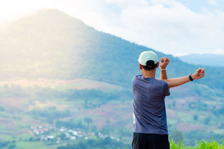 Half-body shot of an Asian male runner in a blue shirt and hat standing warm up in preparation for a jogging run. It is located on a high cliff with beautiful mountains in the background.