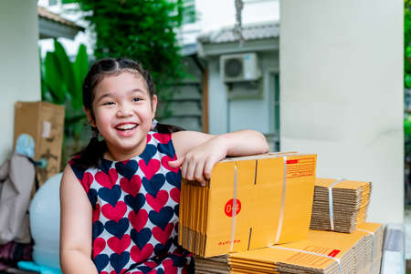 Asian girl preparing a brown postal box for delivery.