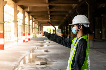 female construction engineer Asians wearing safety hats and green vests stand to watch work and point fingers at a construction site. Standard-Bild