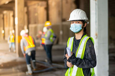 Young Asian female engineer wearing a medical mask to cover her mouth and wearing a white safety helmet Hand holding paper, standing in the Construction Zone, looking at the camera. Standard-Bild