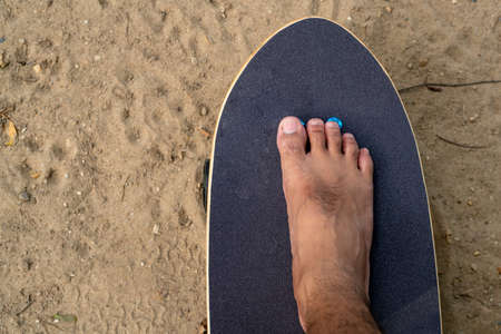 men's feet Without shoes, stepping on a black Surf Skate in the sand in the park. Standard-Bild