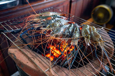 Big fresh prawns laying on the grill, being burned to turn orange, are a very tasty part of Thai food.