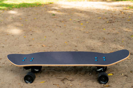 A black Surf Skate has a black top and black wheels lying on the sand in a park.
