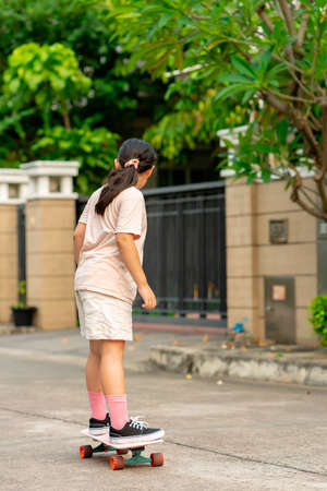 Behind the long hair Asian girl wearing a pink shirt wearing shorts, playing surf skating in front of my house in the evening, play surfskate
