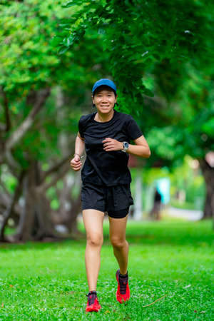 Asian female runners in black sportswear are practicing running in a park, the back is blurry. Standard-Bild