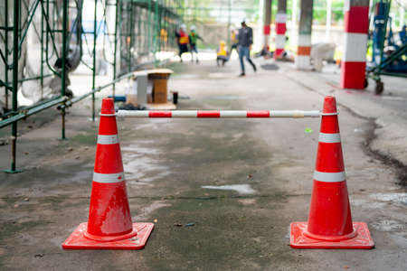 An orange rubber cone was placed as a defense against a no-walk area. while walking in the construction area