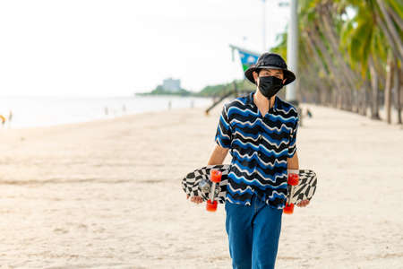 Asian men wearing striped shirts wearing jeans walking holding a surf skate In the area of Bangsaen beach happily On a clear day, Bangsaen, Thailand