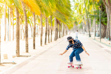 A young Asian man in a striped shirt and trousers is figure skating on a beach filled with coconut palms, during a clear sky time. and no people beach , surf skating, Bangsaen, Thailand Standard-Bild