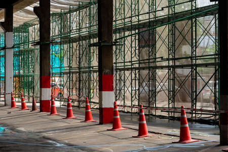 An orange rubber cone was placed as a protective line between the steel frame and the walkway in the construction area. Standard-Bild