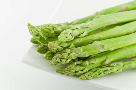 fresh green raw asparagus on white plate
