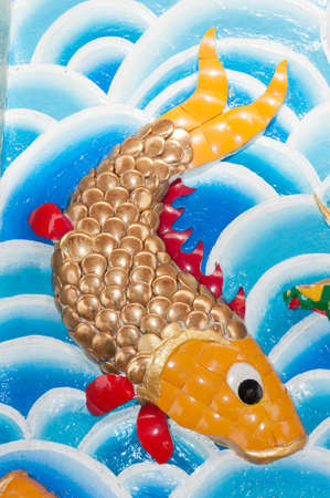 Gold fish at Chinese temple wall in thailand photo