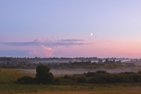 summer fog and the beautiful evening moon in a landscape photo