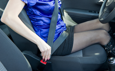 fastens: Attractive young woman in car fastens seat belt