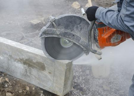 stone cutter: Worker cutting stone block by cutter machine. Stock Photo