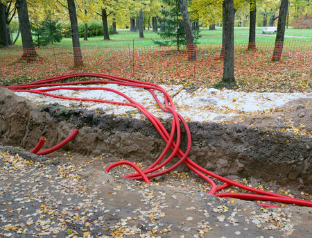 Plastic pipes containing electric cables, repair work in the park Фото со стока