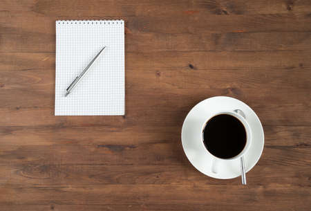 old notebook: cup of coffee and notebook on old wooden table