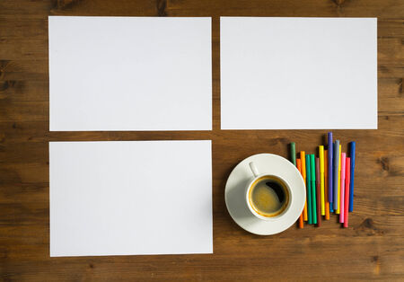 three colored: Three sheet of paper, cup of coffee and colored markers on the table