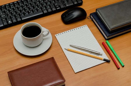 key pad: keyboard, cup of coffee and office supplies laying on the board.
