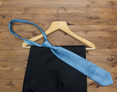 clotheshanger: wooden hanger with tie and trousers on old wooden background Stock Photo