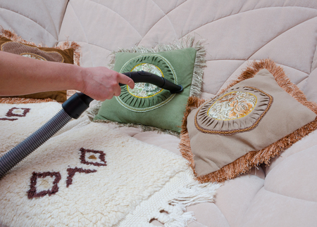 sofa vacuuming with vacuum cleaner at home