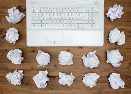 wads: business concept. Laptop, sheets of paper and crumpled wads on table.