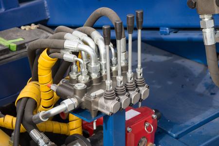 tablero de control: Tubos hidráulicos, accesorios y palancas en el panel de control del mecanismo de elevación