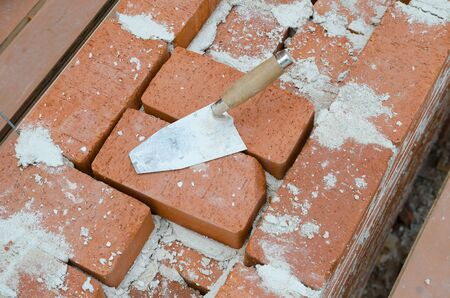 clay brick: Mason bricklaying background with trowel and clay brick blocks