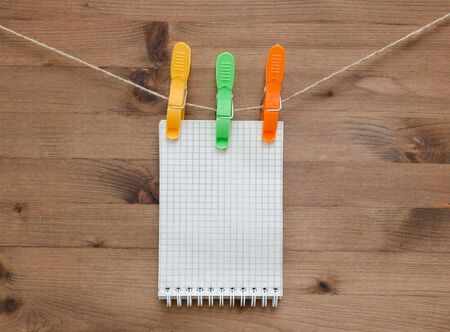 old notebook: Hanging notebook  with colored clothespins on old wood background