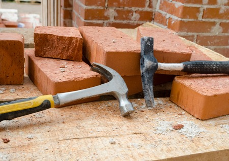 clay brick: Mason bricklaying background with two  hammers  and clay brick blocks