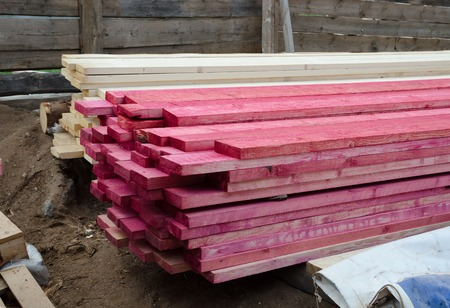 treated board: building supplies, stacked wood boards treated with antiseptic spray Stock Photo