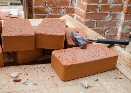 brick mason: Mason bricklaying background with hammer and brick blocks